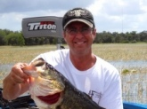 This big female bass was caught during post-spawn after fattening up on Gizard shad on Lake Toho, Florida. I caught her fishing with my friend Brent in a local tournament.  Over 25 boats grouped up on feeding bass in the open water and this female decided to move away from the crowd and feed along the Torpedograss line nearby. Doing likewise, I moved away from the crowd and caught this 10lb,2oz fish pitching a junebug zoom trick worm on 15lb mono to the grassline in 5ft of water.  Caught four others over 4lbs and won with over 22lbs.  It was a grand day to cherish.